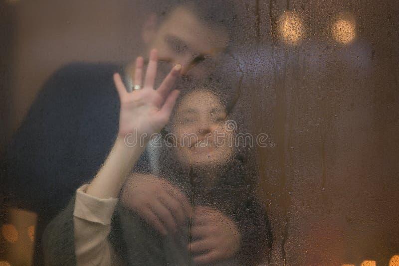 Любя парень обнимает его красивую девушку рисуя сердце на misted стекле стоковое фото