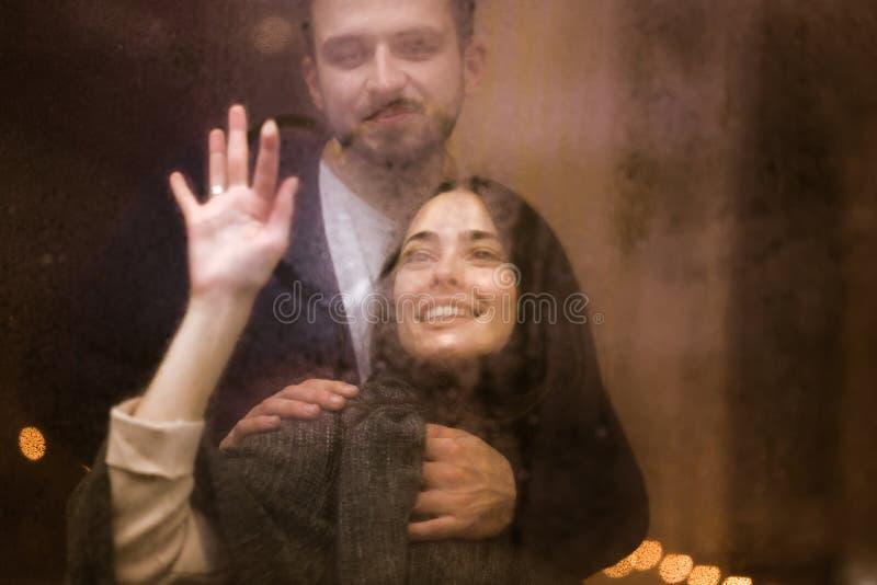 Любя парень обнимает его красивую девушку рисуя сердце на misted стекле стоковое изображение rf
