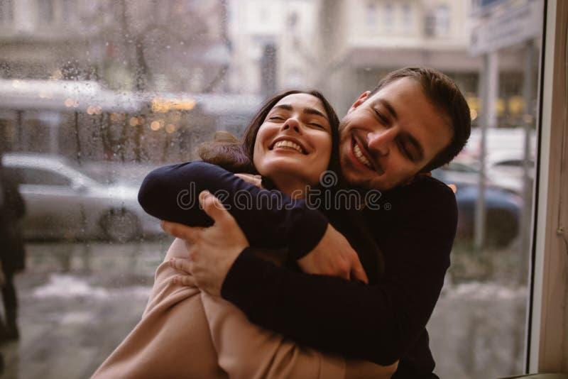 Любя парень обнимает его красивую счастливую девушку сидя на windowsill в уютном кафе стоковые изображения rf