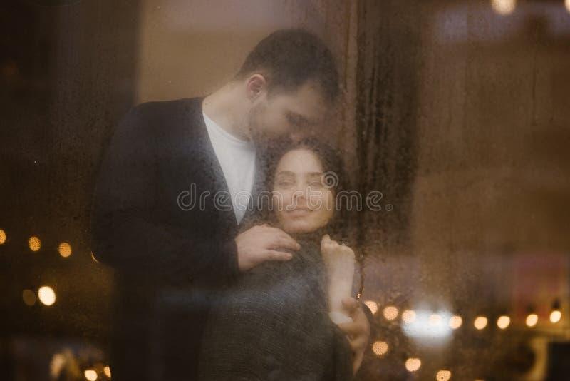 Любя парень обнимает и целует его положение девушки за влажным окном со светами Романтичные пары стоковая фотография rf