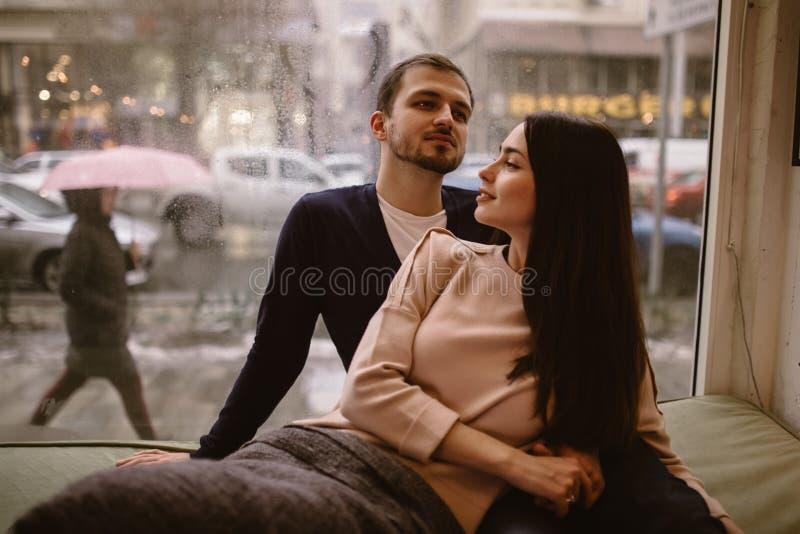 Любя пары Гай и его девушка одетые внутри в свитерах и джинсах сидя близко к одину другого на windowsill внутри стоковая фотография rf
