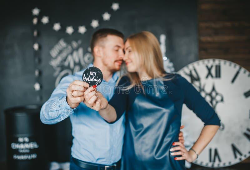 Любя пары держа деревянный круглый знак стоковые изображения