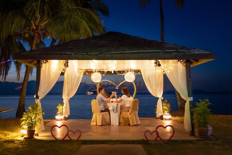 Любя пары есть романтичный обедающий тропическим пляжем стоковое фото