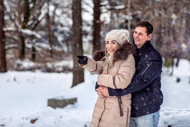 Любя пары обнимая и наслаждаясь outdoors на красивой зиме стоковая фотография