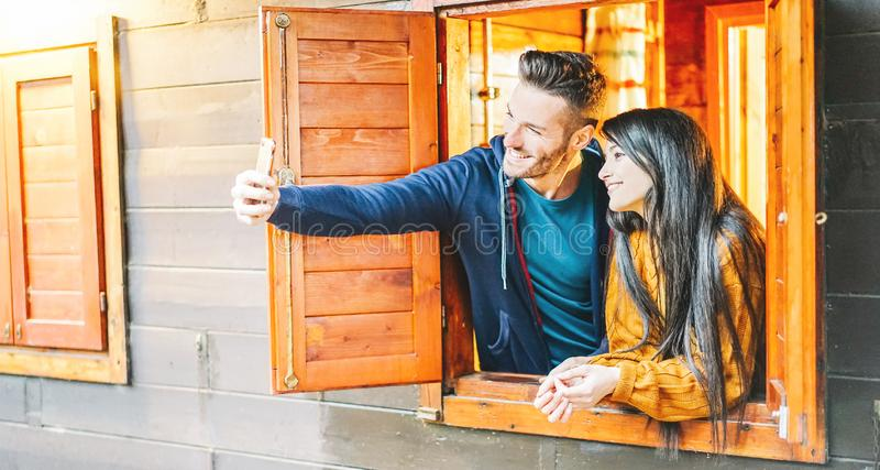 Любя пары принимая selfie вне окна их деревянного дома - молодых любовников фотографируя с камерой мобильного телефона стоковое фото