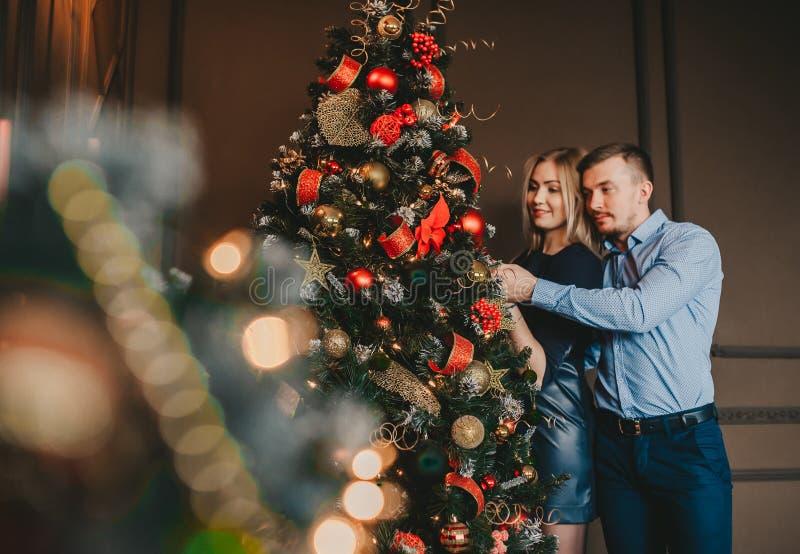 Любя пары принимая selfie около ели украшенной рождеством дома стоковые фото