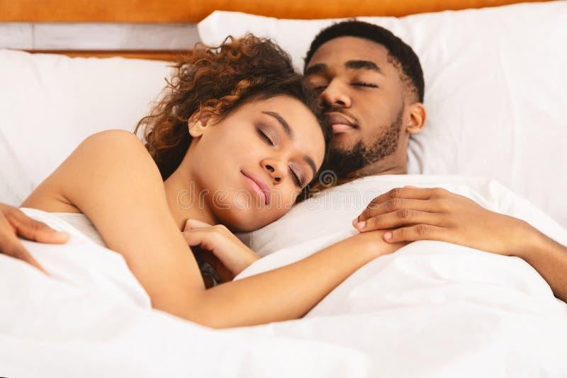 Любя пары спать в кровати и обнимать стоковое изображение
