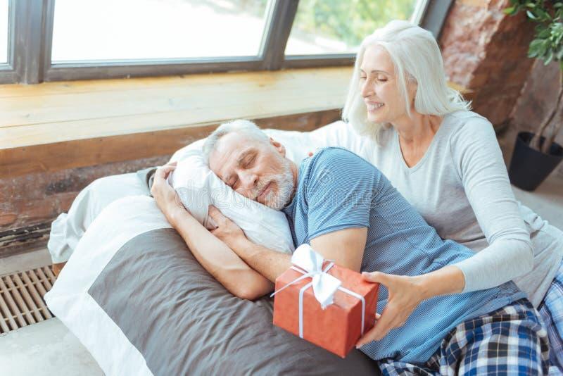 Любя постаретая женщина подготавливая подарок на день рождения для ее супруга стоковое фото