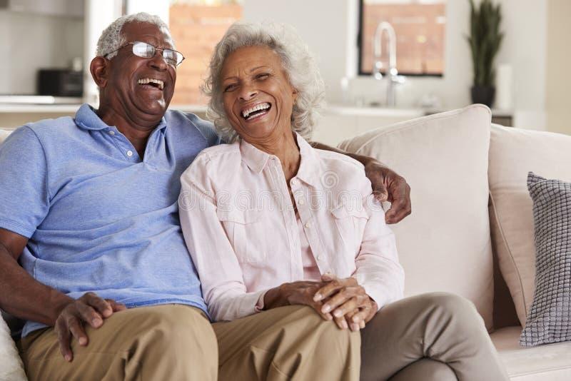 Любя старшие пары сидя на софе дома и смеясь совместно стоковая фотография