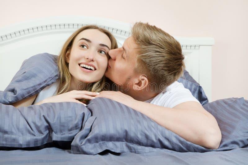 Любя целовать и обнятые пары на кровати в комнате стоковые изображения