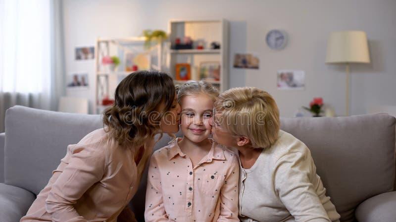 Любя щеки дочери матери и бабушки целуя и обнимать, женские поколения стоковое фото rf