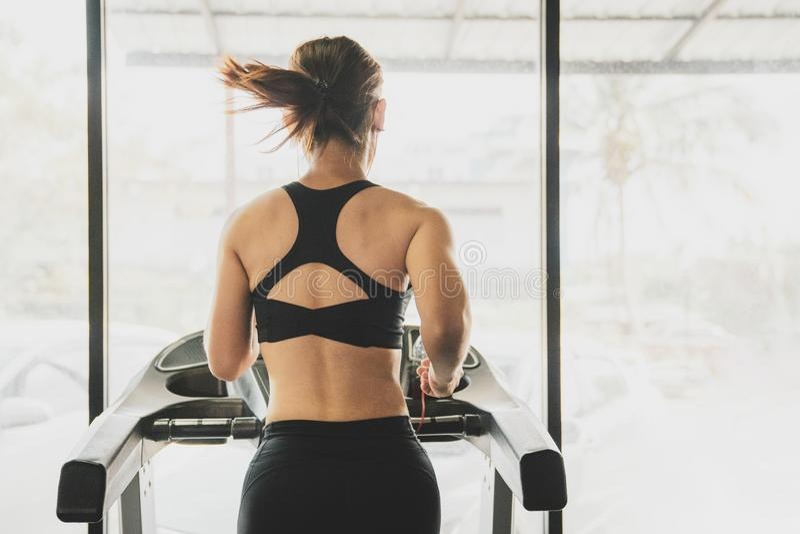 Люди бежать в третбане машины на спортзале фитнеса, разминке молодой женщины в образе жизни спортзала здоровом, молодых людях беж стоковое изображение