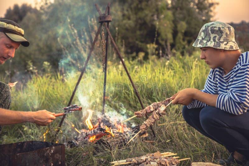 Люди варя outdoors барбекю на огне в летнего лагеря стоковые фотографии rf