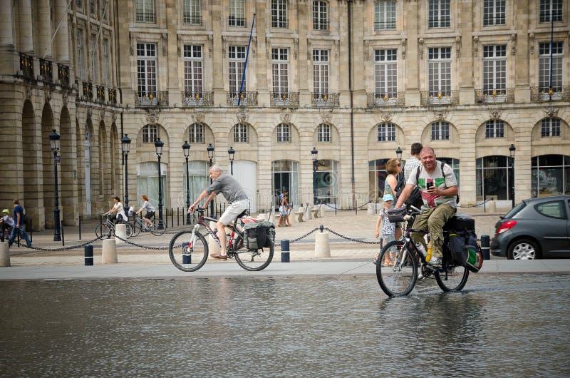 Люди велосипед через зеркало воды места de Ла Фондовой биржи в Бордо Сентябрь 2013 стоковое изображение rf