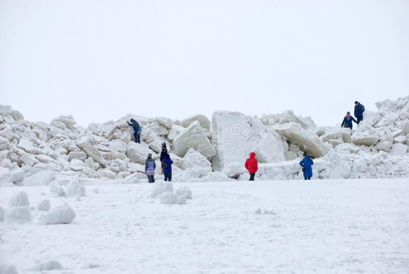 Люди взбираются большие ледяные поля на банке Gulf of Finland Взгляд собора Андрюа апостола Россия стоковые изображения rf