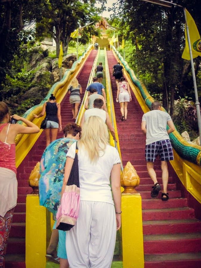 Люди взбираются вверх красные лестницы вверх в Таиланде Туризм стоковая фотография