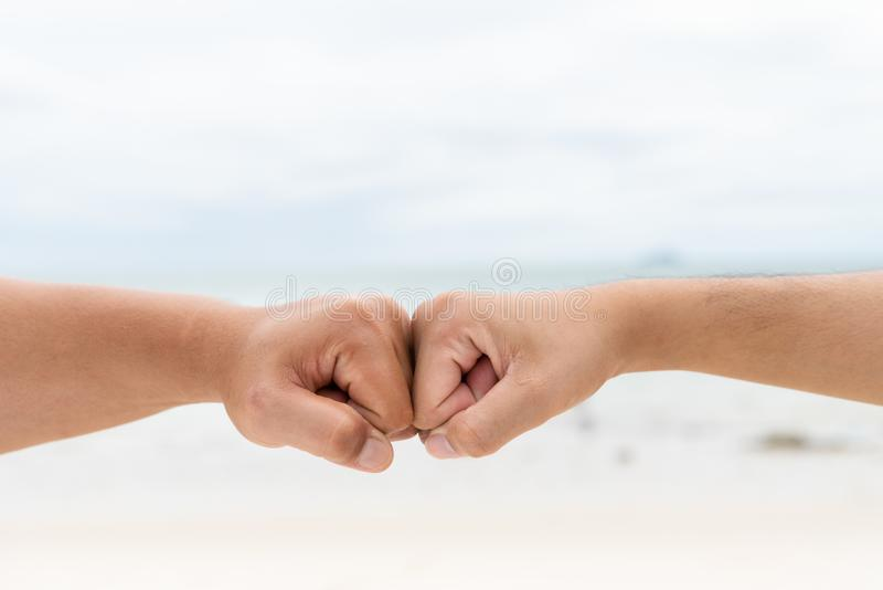 Люди вручают кулак bumping совместно на запачканных море и небе стоковая фотография rf