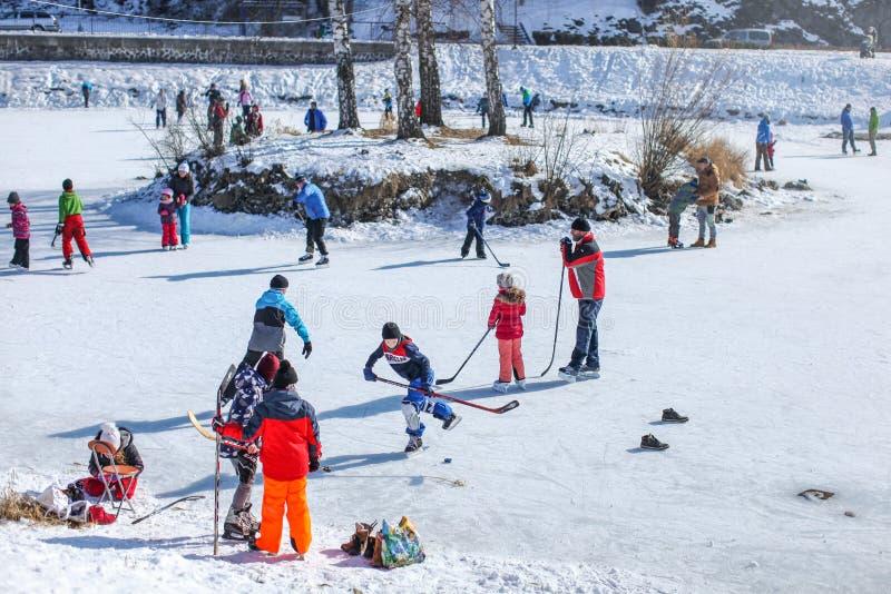 Люди всех возрастных групп наслаждаясь солнечным днем, катаясь на коньках и играя хоккей на льде на замороженном озере, когда тем стоковая фотография rf