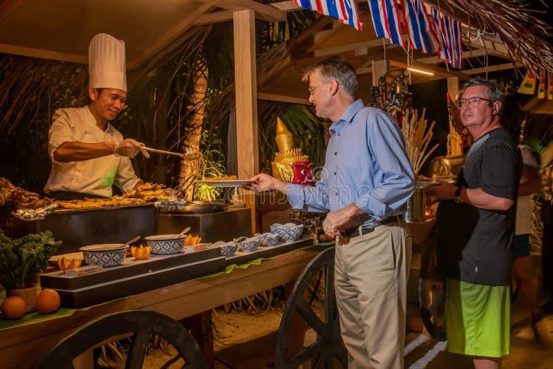 Люди выбирая еду во время международного обедающего кухни outdoors настроенного на тропическом ресторане острова стоковое фото