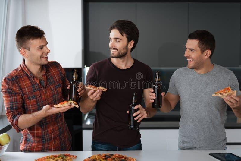 Люди выпивают пиво и едят пиццу в кухне Они говорят и имеют большое время стоковое фото