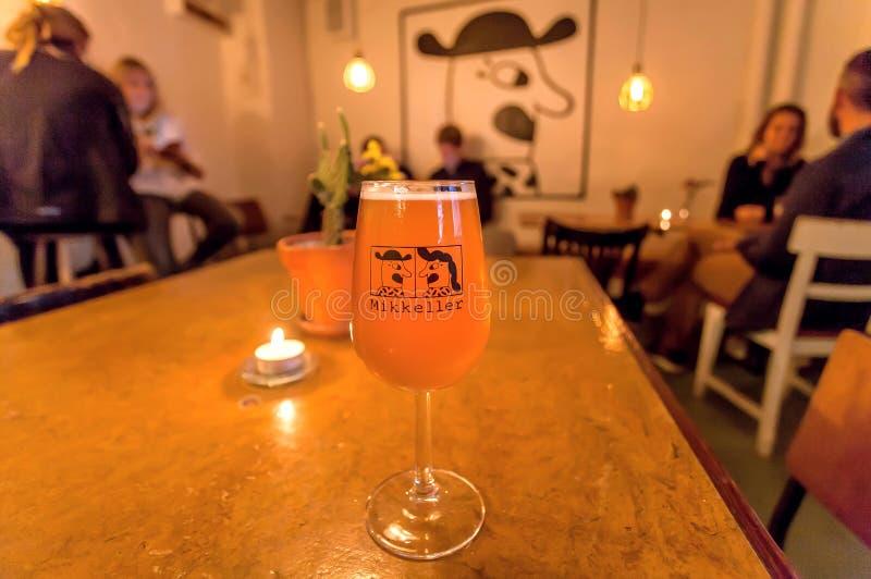 Люди выпивая популярное датское пиво винзаводом Mikkeller с ярким шуточным дизайном стоковое фото rf