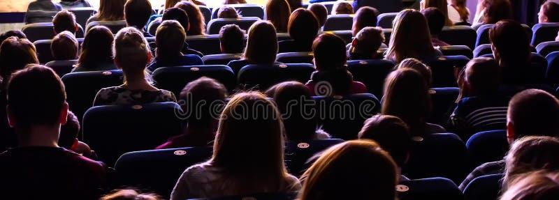 Люди в аудитории наблюдая представление стоковые фотографии rf