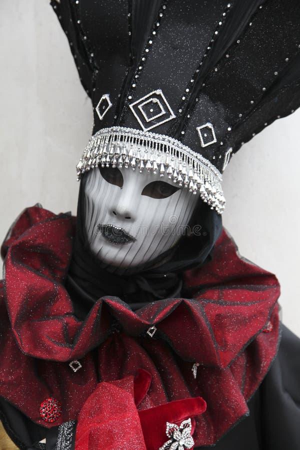 Люди в венецианском костюме масленицы в красочном красных и черных костюме масленицы и маске Венеции стоковые изображения