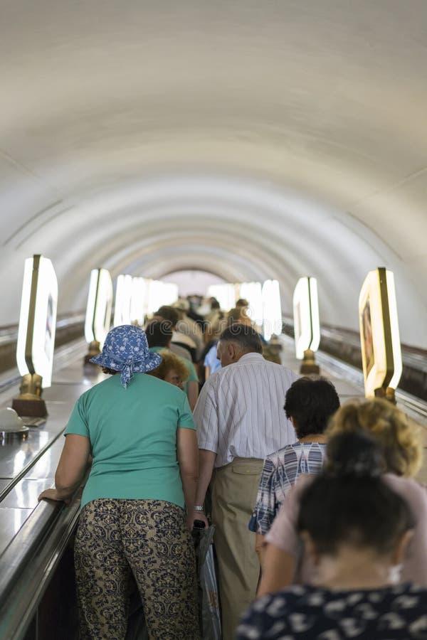 Люди в метро на эскалаторе Толпа людей на лестницах в метро ( стоковые фото