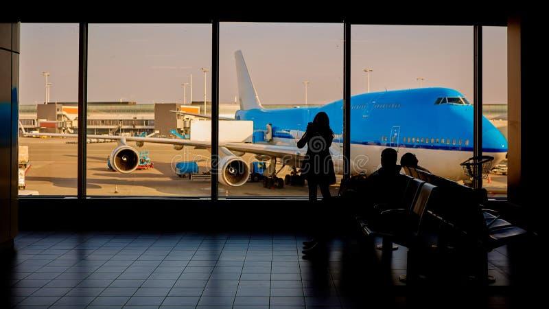 Люди в отклонении аэропорта ждать, силуэт пассажира женщины путешествуя с багажом стоковая фотография