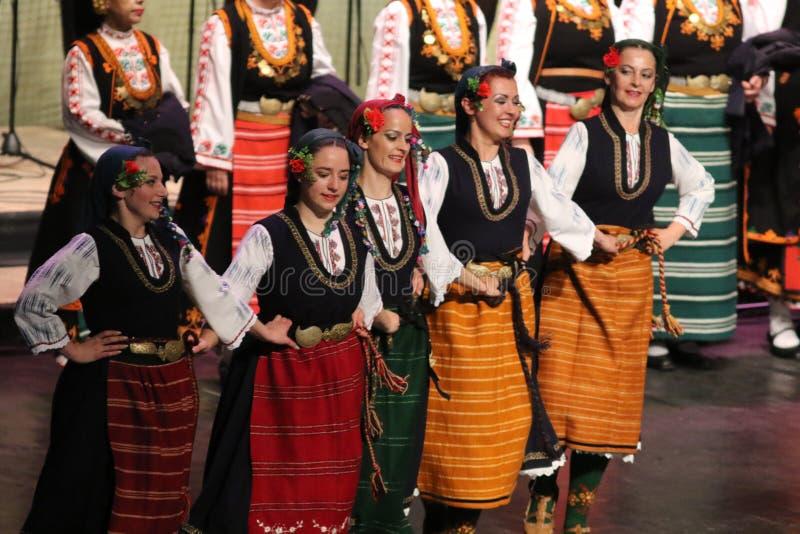Люди в традиционных костюмах фольклора выполняют народный танец болгарское Horo стоковое изображение