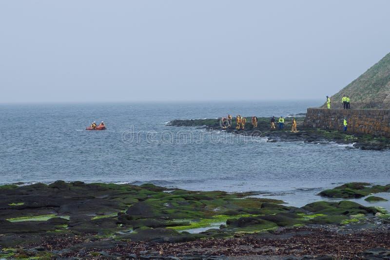 Люди в форме на береге и в спасательных операциях проведения шлюпки на seacoas стоковое фото