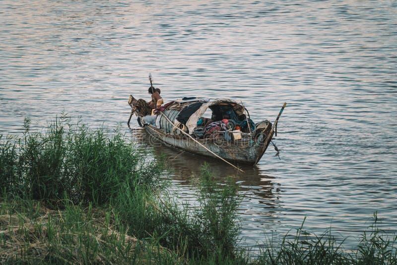 Люди в шлюпке на деревне реки плавая в Камбодже Азии плохие камбоджийские семейные жизни в шлюпке на воде Бедность в юговосток стоковое фото