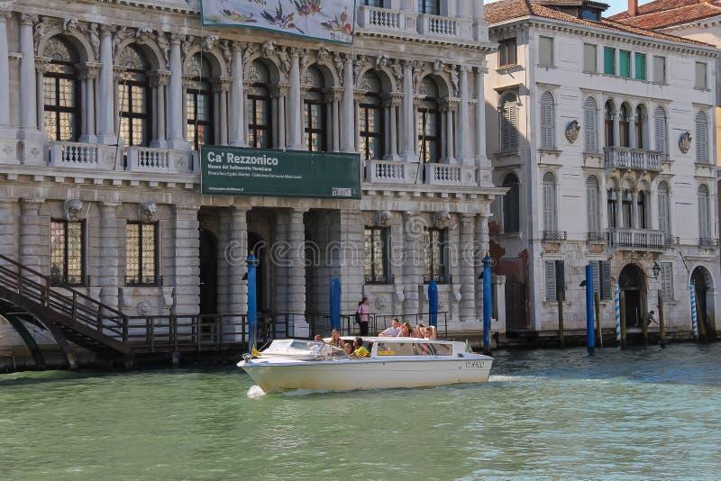 Люди в шлюпке такси на канале Венеции, Италии стоковые фото
