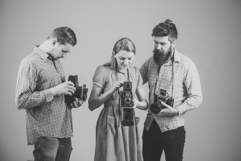 Люди в checkered одеждах, ретро стиле Компания занятых фотографов с старыми камерами, киносъемка, деятельность сбор винограда рес стоковые фотографии rf