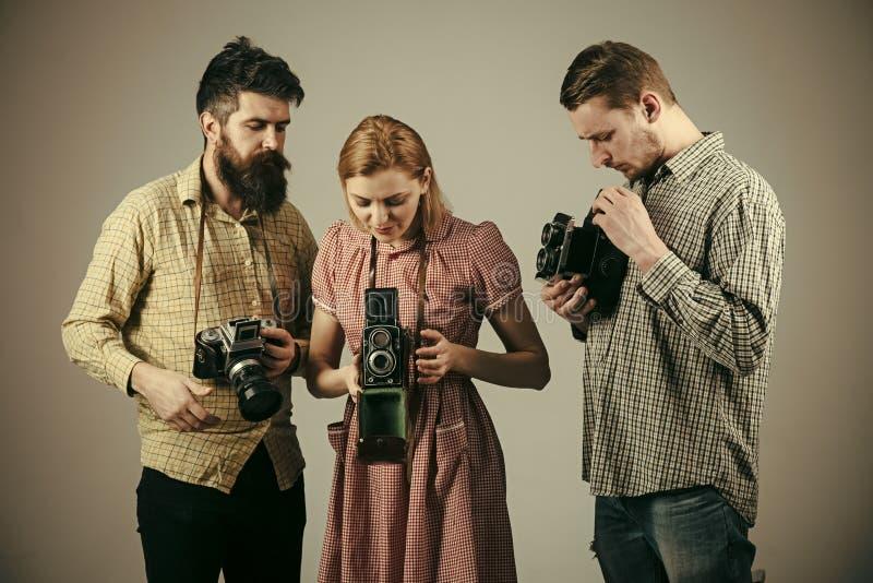 Люди в checkered одеждах, ретро стиле Компания занятых фотографов с старыми камерами, киносъемка, деятельность Люди и женщина стоковые фотографии rf