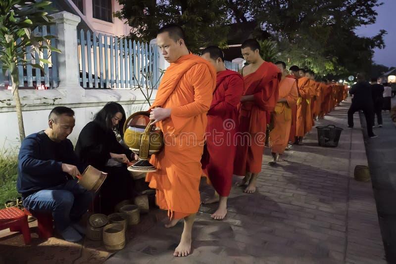 Люди давая милостыни буддийским монахам на улице, Luang Prabang, Лаосе стоковая фотография rf