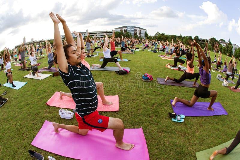 Люди делают представление йоги в занятия йогой группы Атланты стоковое изображение