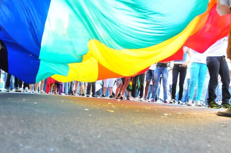 Люди держа красочный флаг lgbt движения стоковое фото