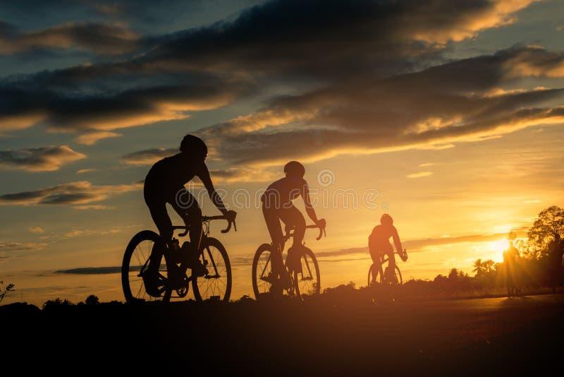 Люди едут велосипеды на заходе солнца с апельсин-голубой предпосылкой неба стоковая фотография
