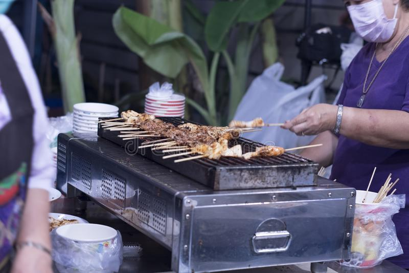 Люди жарят в духовке свинину satay, креветку satay, каракатицу стоковые фото