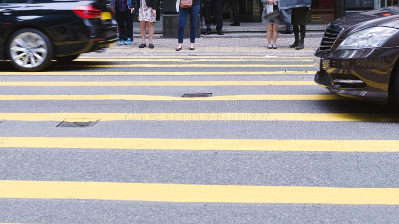 Люди ждать для того чтобы пересечь улицу, пешеходный переход на занятой дороге, детали ног толпы стоковые изображения rf