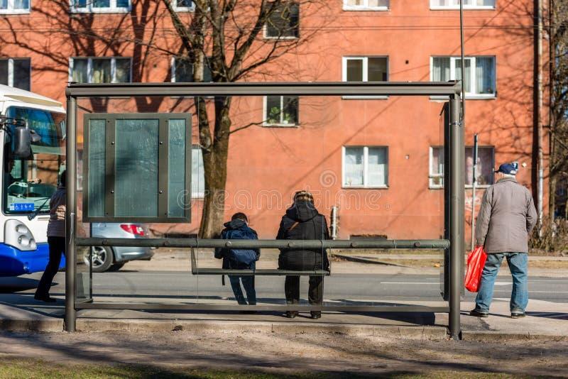 Люди ждать шину на автобусной остановке задний взгляд стоковые изображения