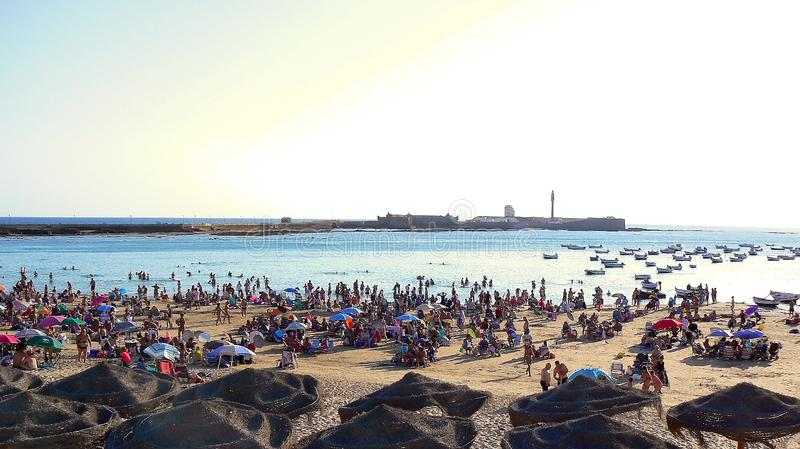 Люди загорая на заходе солнца на пляже Ла Caleta в заливе Кадиса, Андалусии Испания стоковая фотография rf