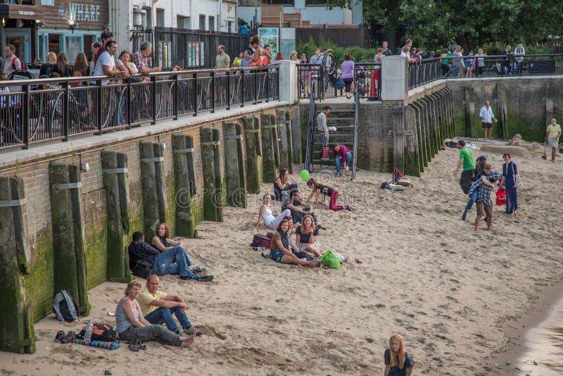 Люди загорая на песчаном пляже сбоку реки Темза на южном береге стоковые фотографии rf
