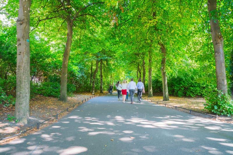 Люди, запачканные в движении, идя leisurely вдоль Пэт парка города стоковая фотография