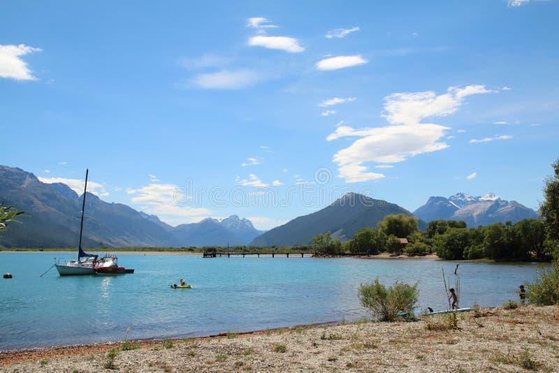 Люди играя в воде на озере Wakatipu, Glenorchy, южном острове, Новой Зеландии стоковые фотографии rf