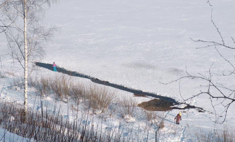Люди идут вдоль банков замороженного реки в парке зимы стоковое изображение