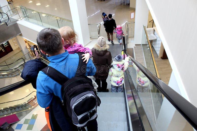 Люди идут вниз с эскалатора в торговом центре стоковые фото