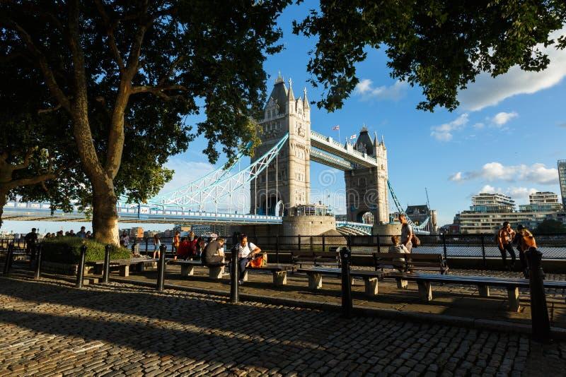 Люди идут на обваловку около моста башни переход реки, выравниваясь стоковые изображения rf