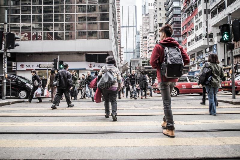 Люди идут через дорогу, залив мощеной дорожки в Гонконге стоковое фото rf